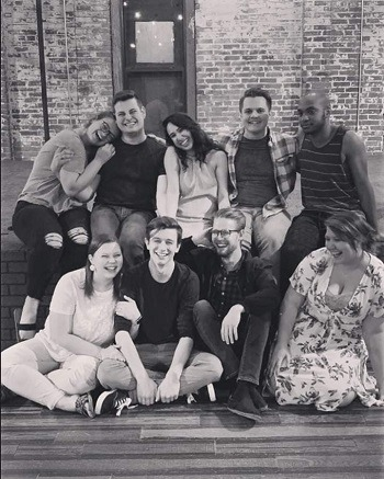 A black and white photo of a theatre cast gathered together.