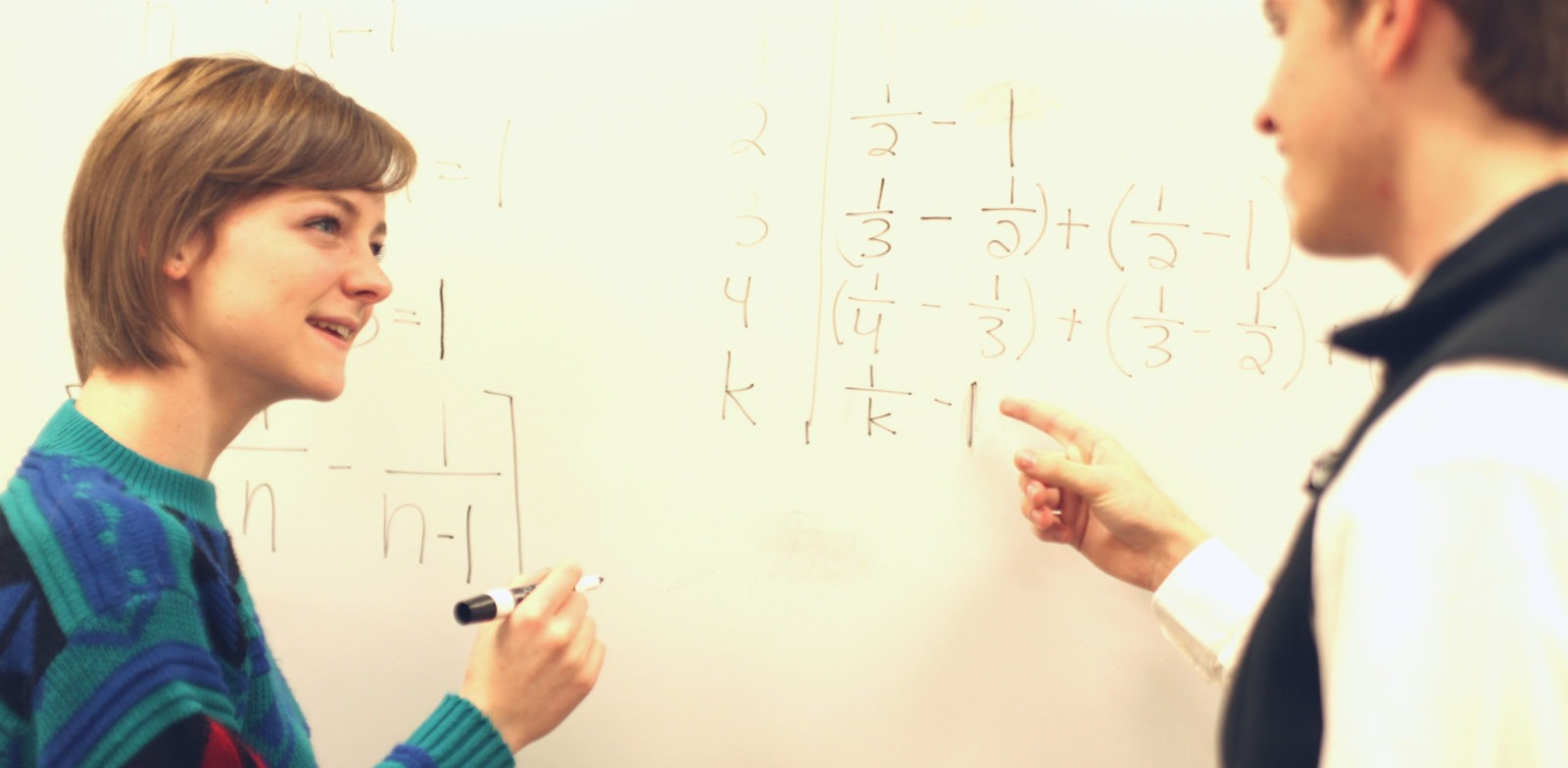 Professor and HSU solving math problems on white board