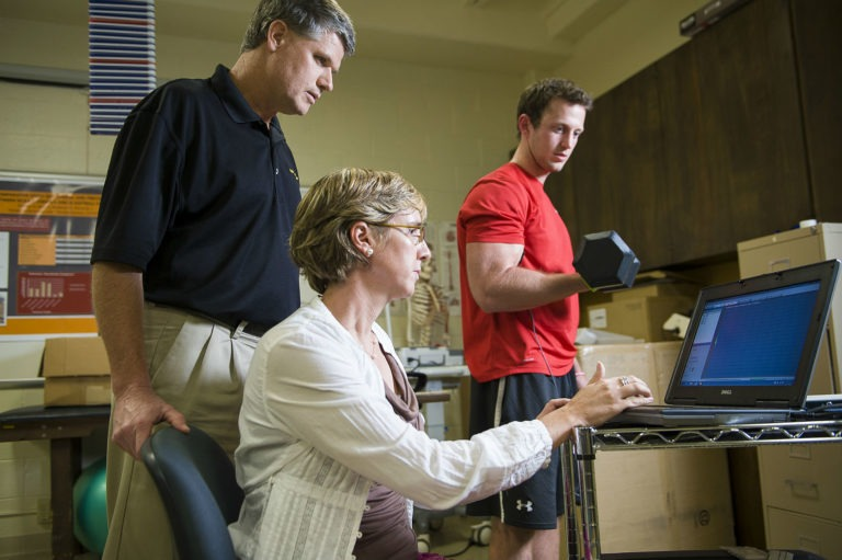 HSU student lifting weight while professor uses pc device to measure performance