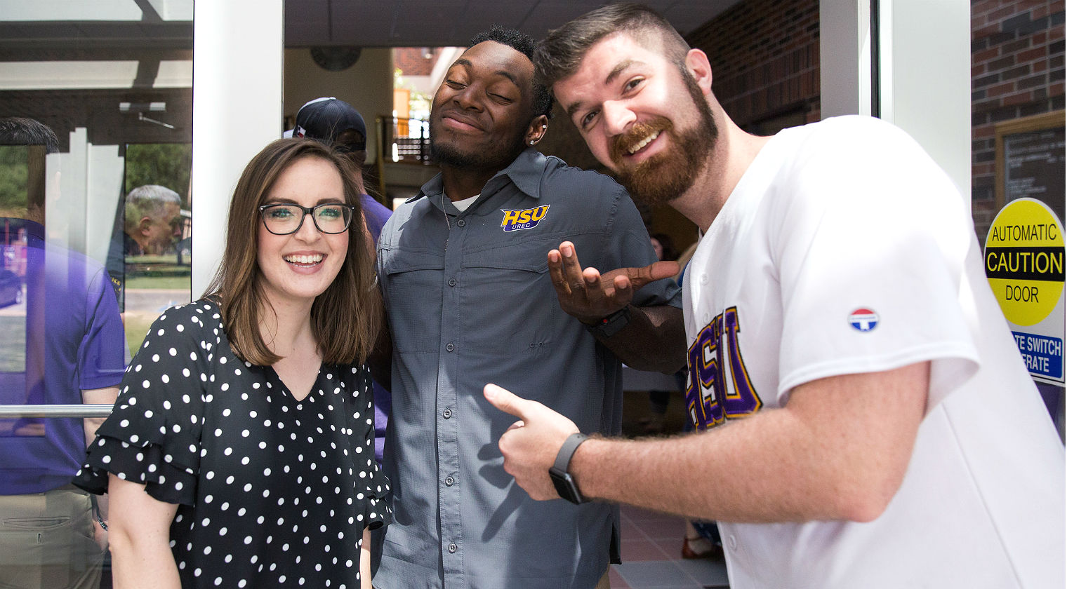 HSU students smiling in front of Student Services building