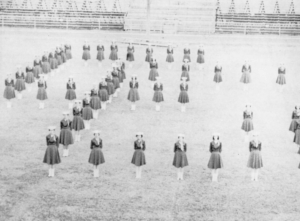 The Cowgirls form a C and a G to represent the name of their organization during a 1959 football game.